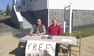 Bro. Wayne and Bro. Matthew giving away Bibles.